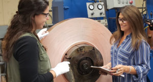 Denise Marcoccia, right, owner and CEO of Clad Metal Specialties, speaks with production engineer Lindsey McErlean in front of a rolling mill loaded with copper clad steel.